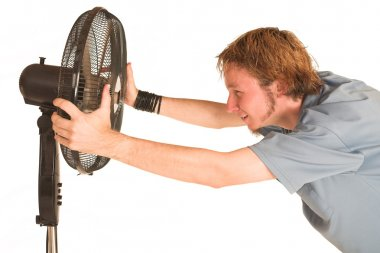 Man with blue shirt cooling down in front of a fan.