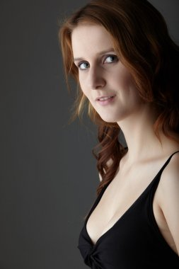 Young caucasian adult redhead woman with green eyes and very fair skin in a little black dress on a neutral grey background