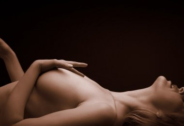 Artistic low key image of a natural nude female form