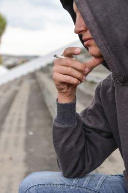 pensive and worried teenage boy with black hoodie is smoking cig