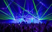 Sziluettek és zenészek a koncert és a fénysugarak