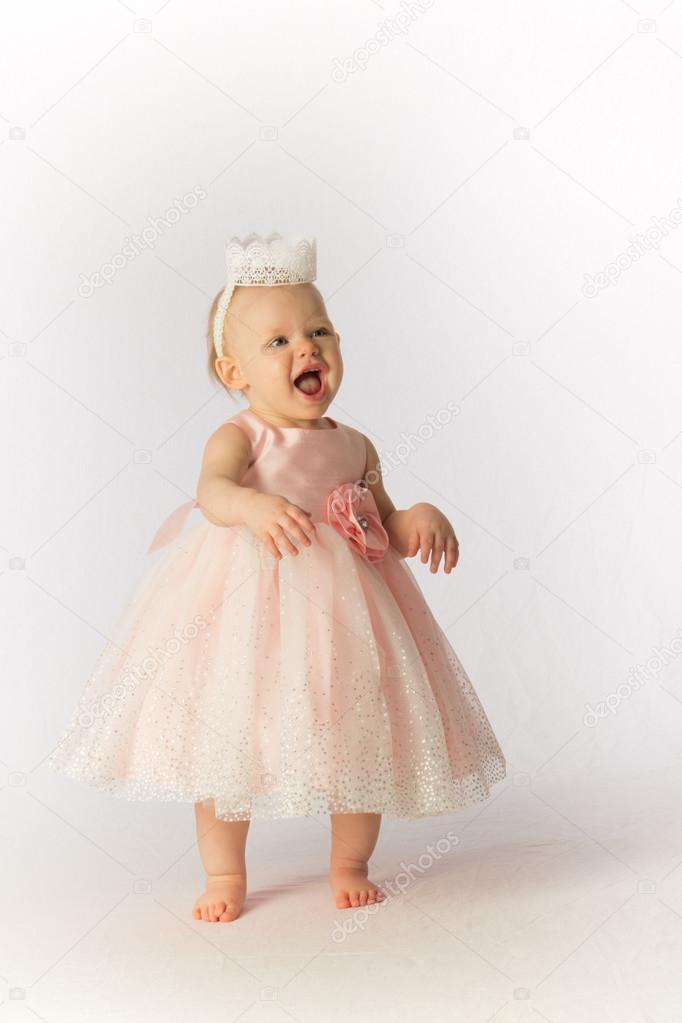 lacht ein glücklich Kleinkind Mädchen trägt eine rosa Party-Kleid ...