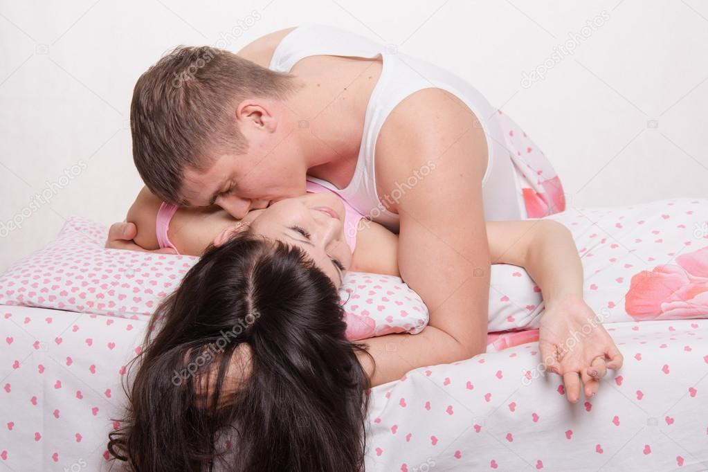 Молодая взрослая целуются в кровати парень и девушка фото