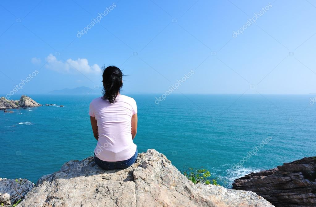 Back of  woman sit on seaside rock