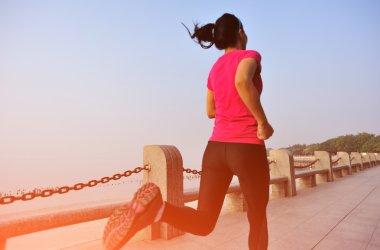 Woman jogging at sunrise seaside