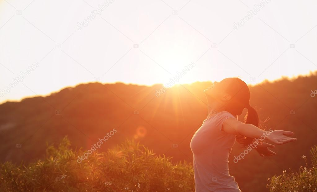 Hiking woman open arms to the sunrise
