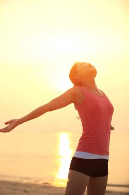 Woman opening arms under the sunrise