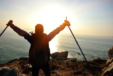 Woman open arms to sunrise at sea