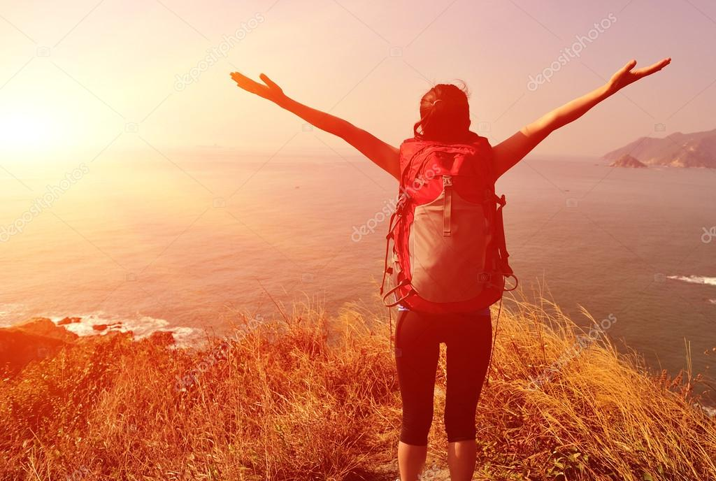 Woman hiker open arms to sea