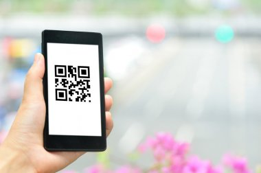 Woman hand hold smart phone with coupon QR code