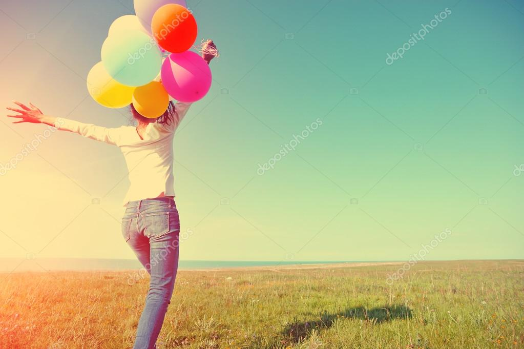 Young woman running with colored balloons