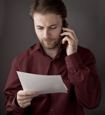 Forty years old office worker reading paper documents during mobile phone conversation - checking terms of agreement