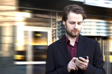 Forty years old businessman standing outside modern office building looking on a mobile phone