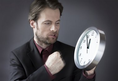 Forty years old frustrated businessman punching a clock with his fist - office worker under time pressure before deadline concept