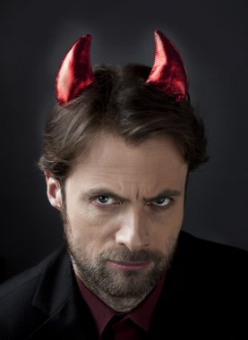 Man in suit with devil horns. Concept of a nasty, cruel, demanding boss or unfair competition in business.