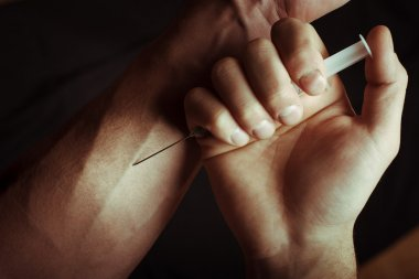 Hand with heroin syringe. Close-up photo.