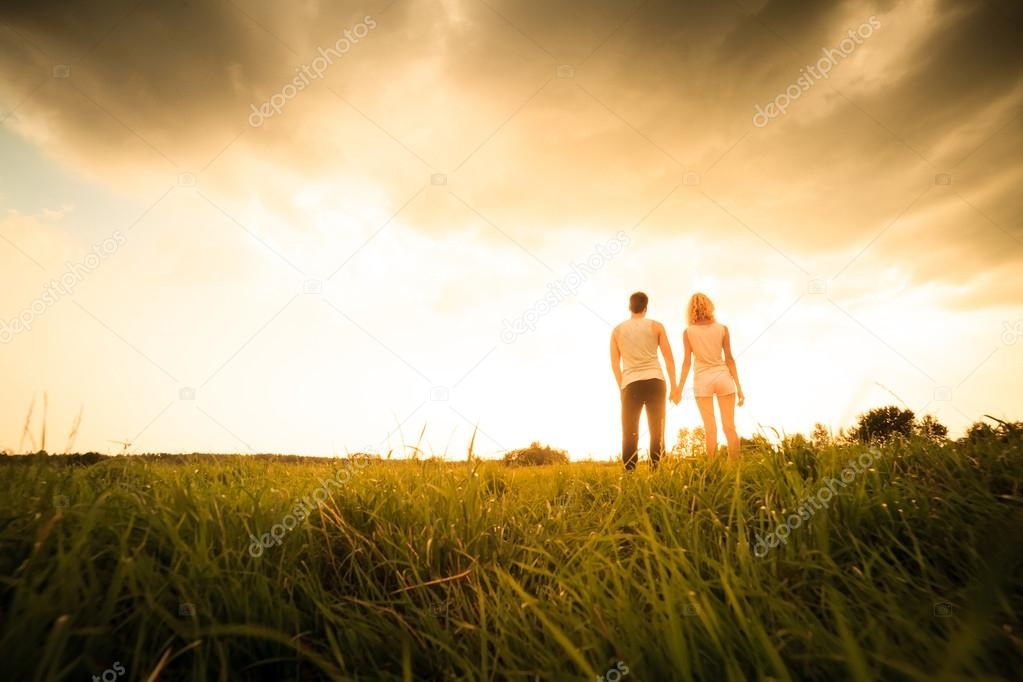 couple walking through the field and holding hands