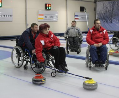 Team of young disabled people on game in curling