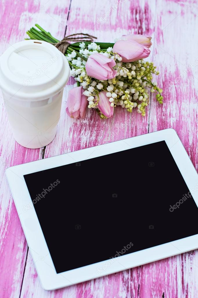 a tablet computer, a glass of coffee and  lilies of valley and t