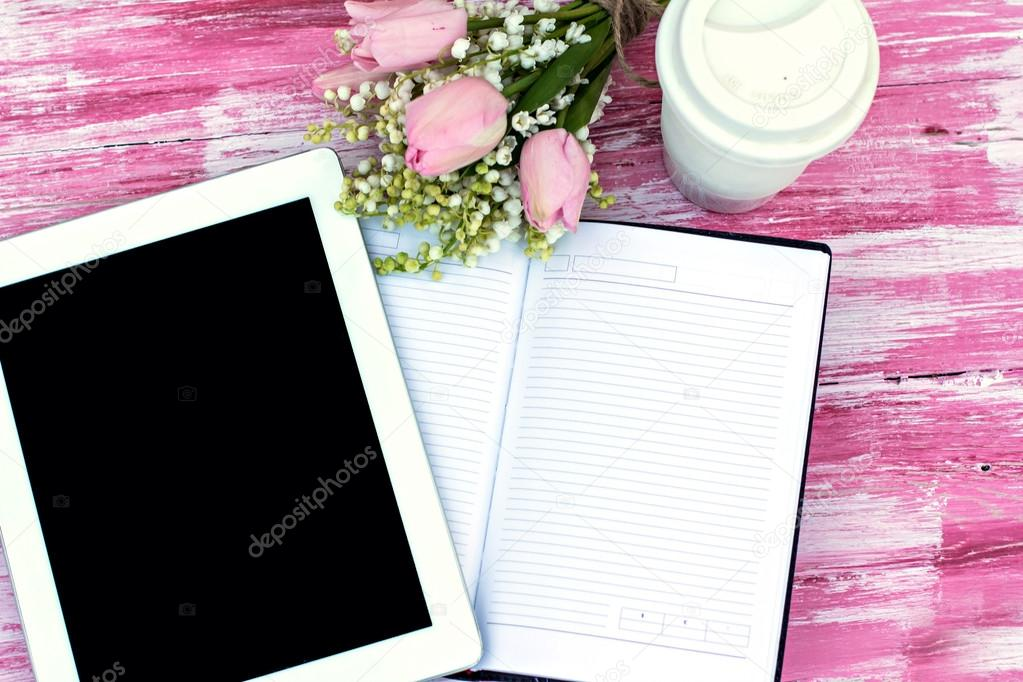 diary, a tablet computer, a glass of coffee and  lilies of valle