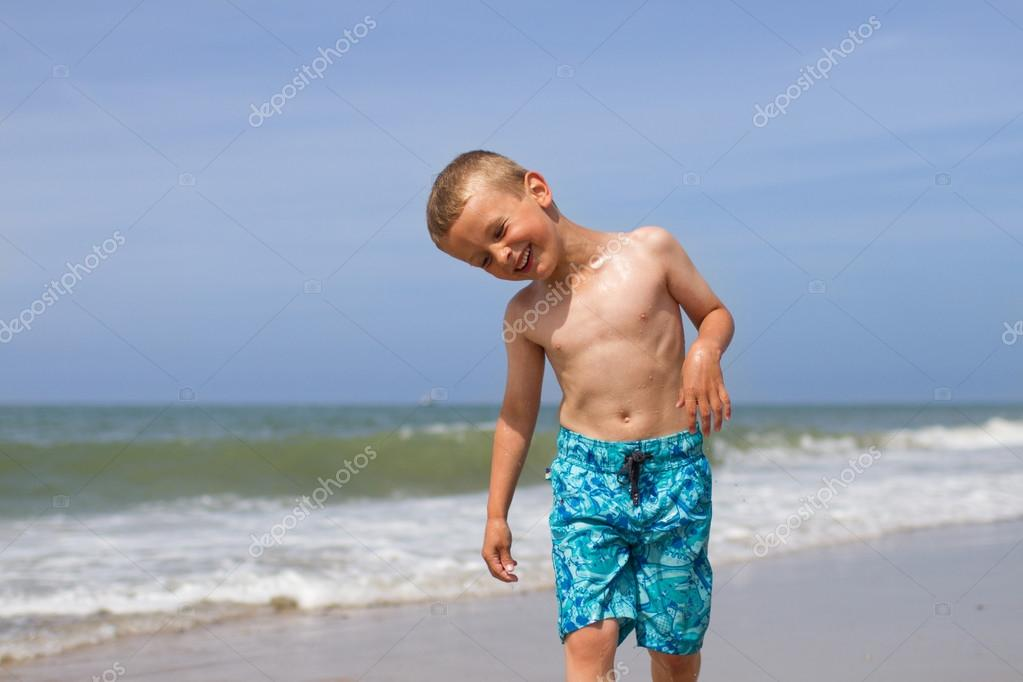 Laughing boy on beach after a swim