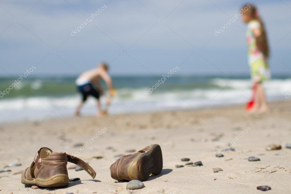 Kids sandals and children at the beach