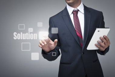 Businessman with tablet pushing on a solution button