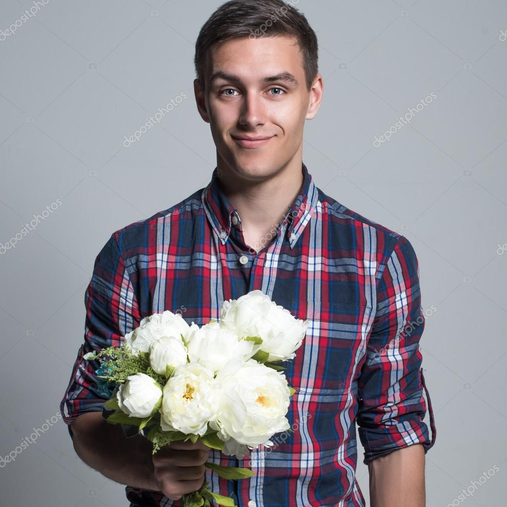 Young beautiful headsome attractive enamored man casual stule with flowers