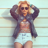 nyári szabadtéri Vértes portré fiatal elegáns divat elbűvölő asszony vagy a lány feltett napos utcai farmer kabát és fehér fal mellett állandó napszemüveg