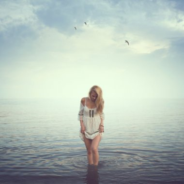Beautiful girl in the water. Beach, sunrise, cold morning. concept loneliness love sadness romance