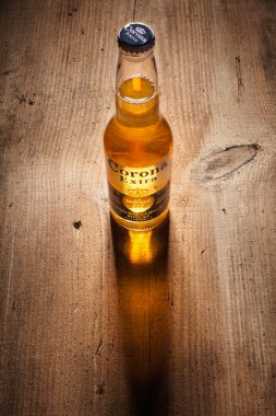 Gold Corona Extra beer bottle with long shadow on wooden boards
