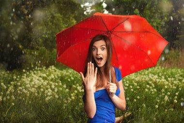 Girl with red umbrella under summer rain
