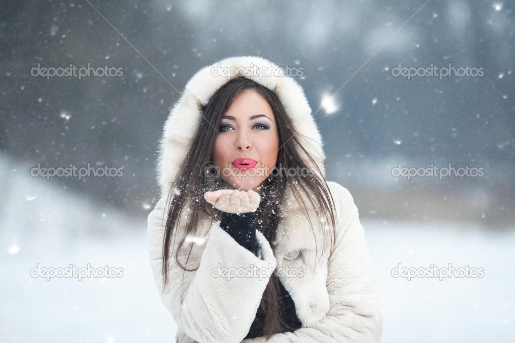 Feliz hermosa joven soplando los copos de nieve de su mano en un día de  invierno — Foto de KateIgnatenko ee70bc76d53