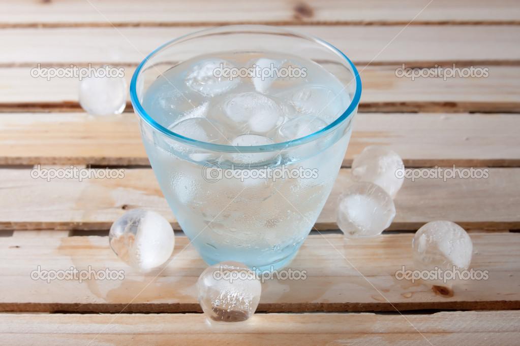 e3081edd27 Bicchiere pieno di acqua pura con palle di ghiaccio su un legno — Foto di  staroshchuk