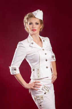 Alluring blonde woman in pin-up retro sailor costume with bright makeup and hairstyle. Beaotiful girl stewardess