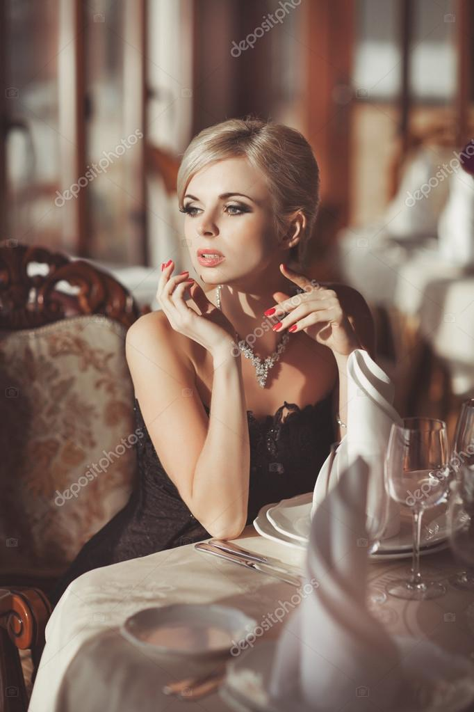 2a15d6c49 Beautiful sexy woman in restaurant cafe blonde girl rich stylish lady  resting at retro villa hotel with hairstyle makeup jewelry in evening dress.  pretty ...