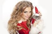 schöne Weihnachtsfrau im Weihnachtsmann-Kostüm mit Katze.