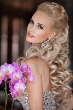 Beautiful blonde young woman with orchid flowers bouquet.