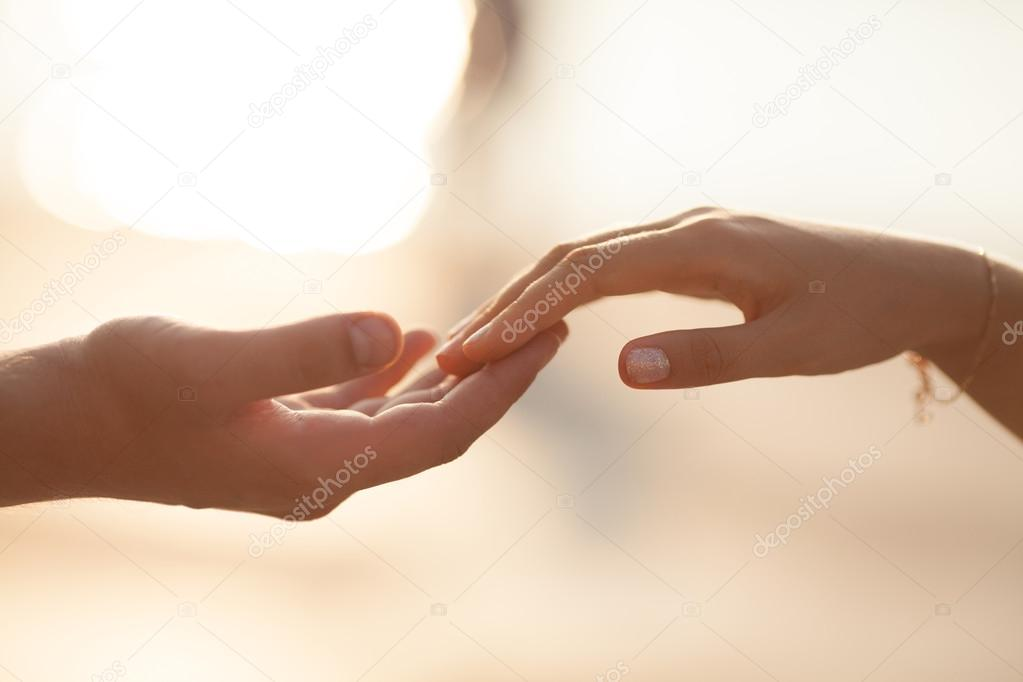 Wedding couple holding hands on sunset.