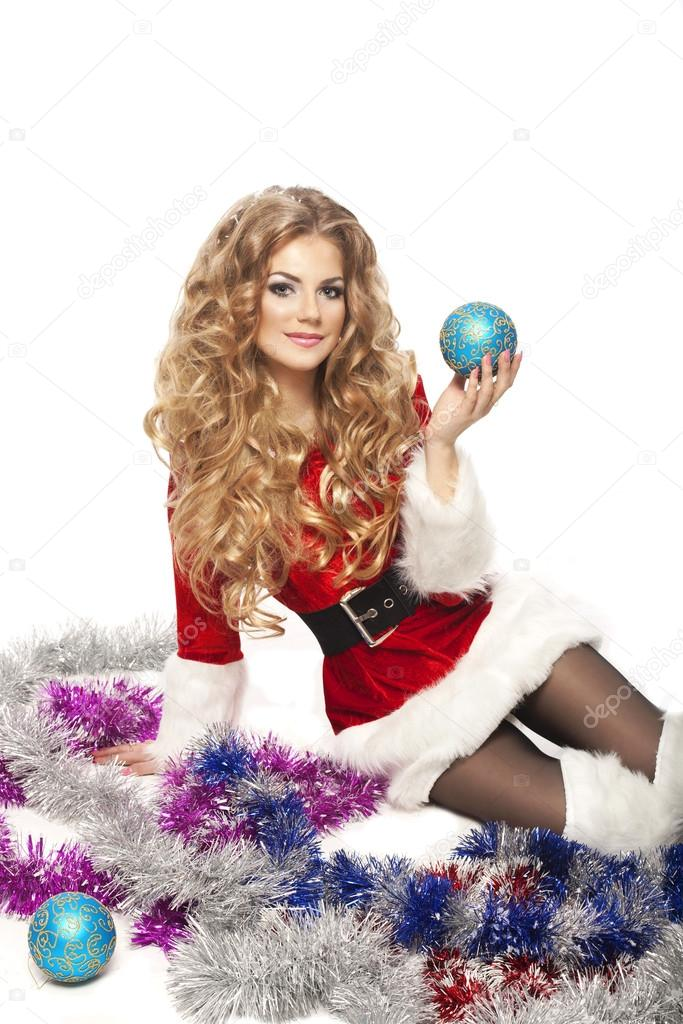 Beautiful Christmas woman in Santa Clause costume holding decorative ball.