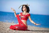 Fotografie schöne indische Frau tanzen mit goldenen Schwert im freien