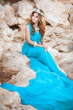 Beautiful Fantasy woman in long blue dress and seashell wreath