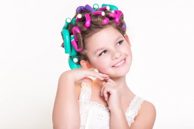 Lovely little girl portrait in curlers and pajamas, skincare kid beauty and glamour.