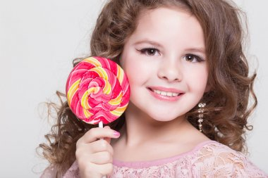 Funny child with candy lollipop, happy little girl eating big sugar lollipop, kid eat sweets. surprised child with candy.