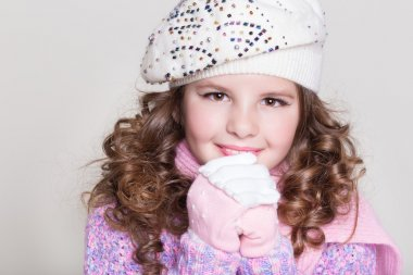 Lovely little girl in winter knitted hat pink scarf gloves and colorful cozy sweater.