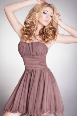 Fashion lady, sensual blonde woman with shiny curly silky hair in elegant dress.