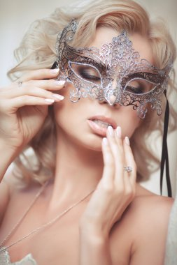 Vogue style portrait of beautiful delicate woman in venetian mask and fashionable dress.