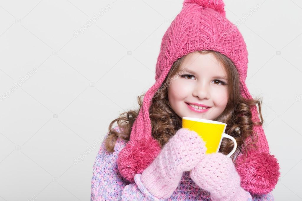 ff50ee49de80 Beautiful child in winter hat drinking hot chocolate