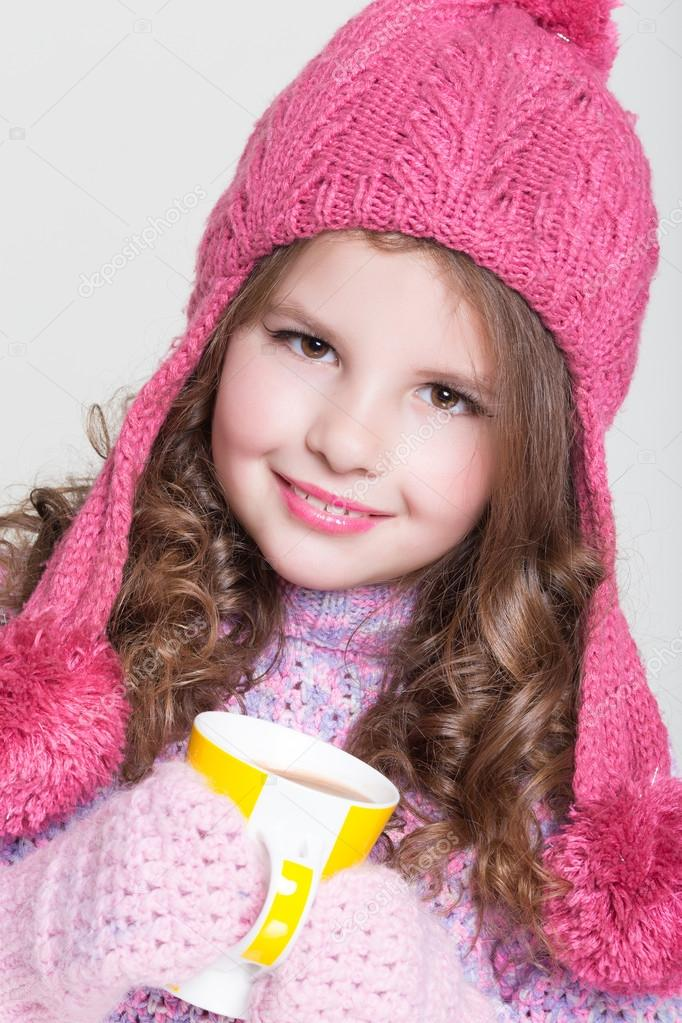 a51267a2064 Beautiful child in winter hat drinking hot chocolate