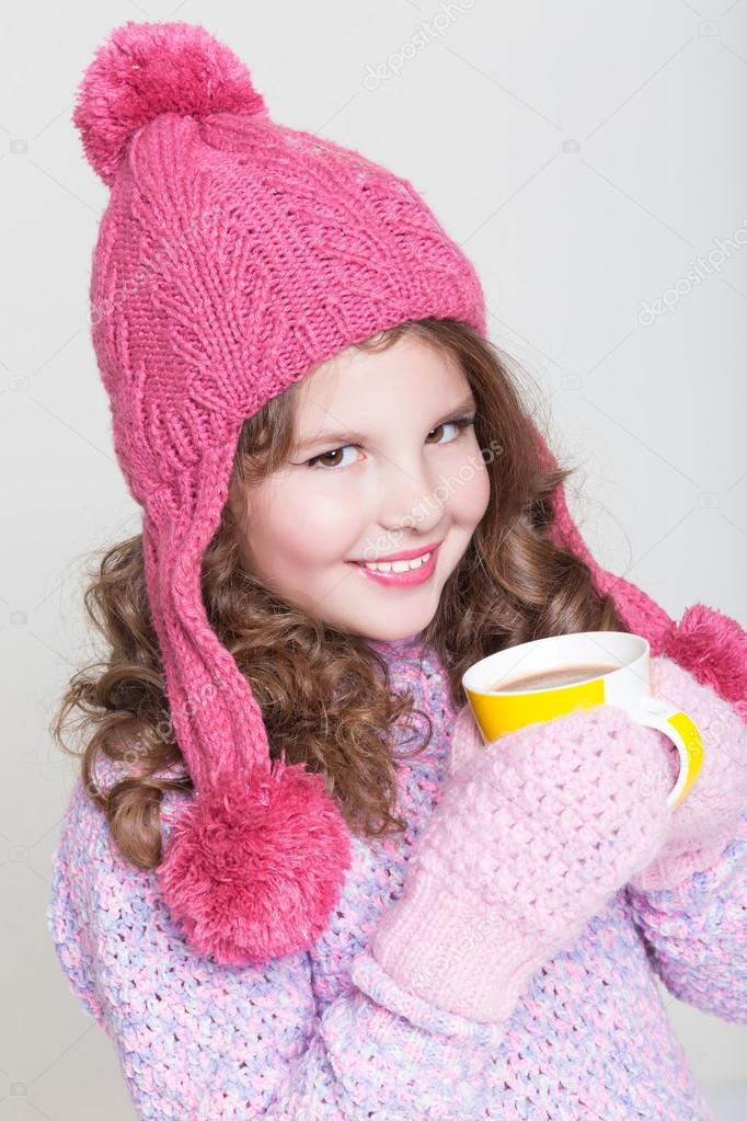 3b55f02d25eb Beautiful child in winter hat drinking hot chocolate